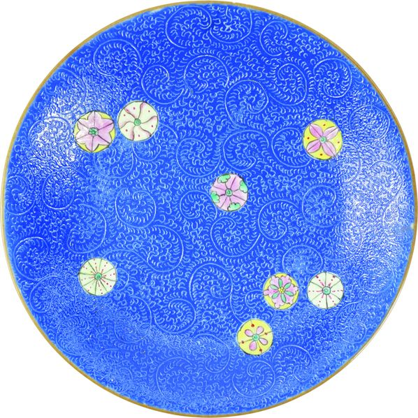 Assiette en porcelaine famille rose à fond bleu sgraffito.