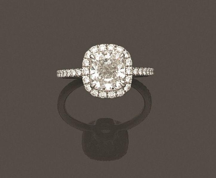 Bague en platine 950 millièmes ornée au centre d'un diamant coussin dans un entourage de diamants ronds de taille brillant.
