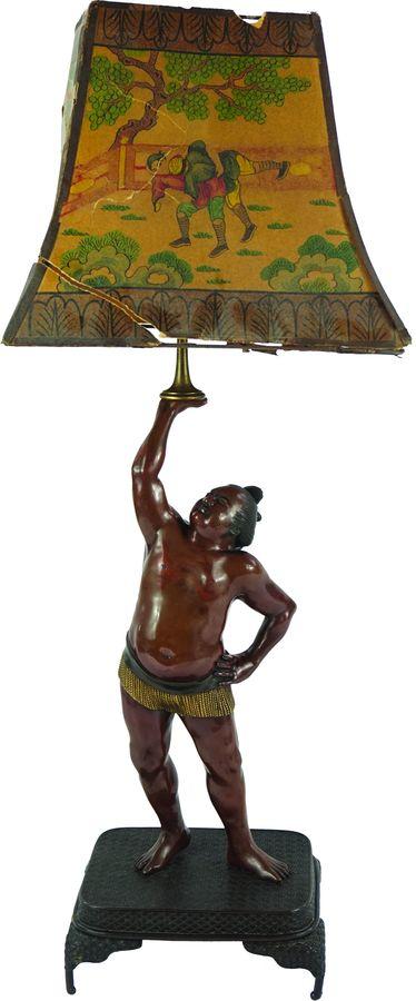 Lampe en bronze  à patine brune partiellement dorée représentant un lutteur Sumo.