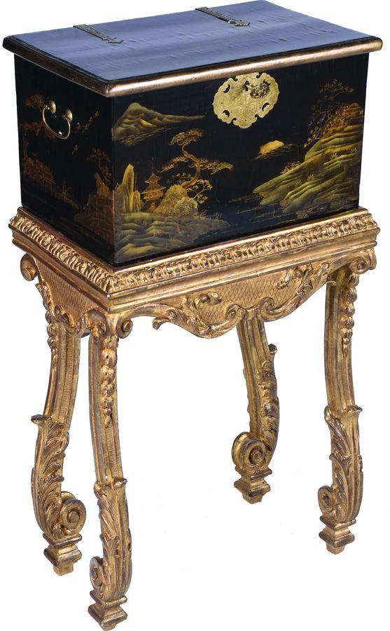 Coffre rectangulaire en bois laqué à décor or sur fond noir de paysages maritimes composés de pagodes, montagnes et pins, dans le goût japonais.