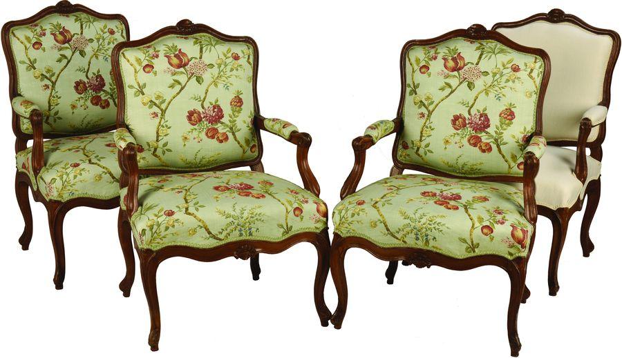 Suite de quatre fauteuils à dossier plat et épaulé en hêtre mouluré et sculpté à décor de fleurettes.