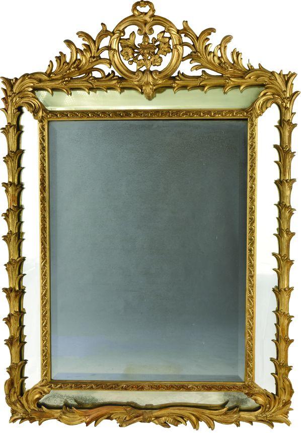 Grand miroir à parecloses en bois doré à décor de feuilles de palmes.