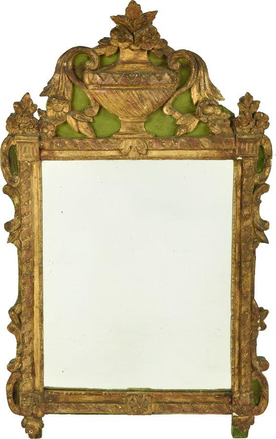 Miroir en bois doré à décor  de colonnettes et enroulements, surmonté d'un fronton à motif de cassolette fleurie.