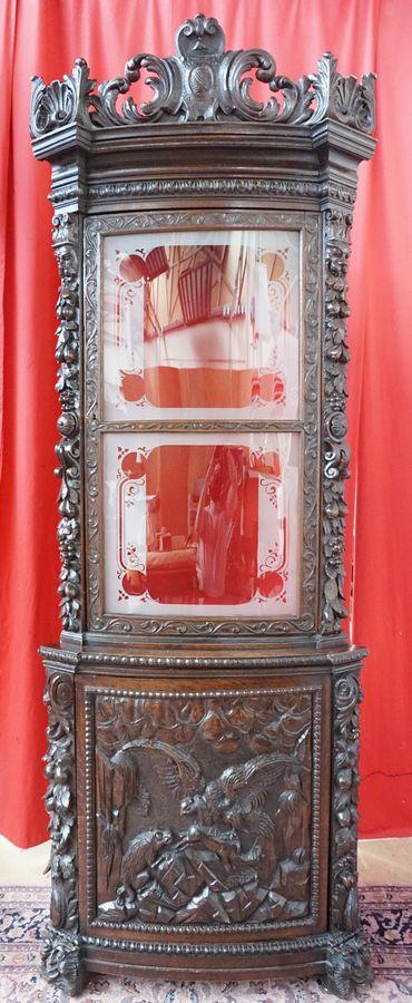 Encoignure en deux corps à décor de style néo-Renaissance de chutes de fruits et mascarons. Le vantail inférieur présente une scène d'affrontement entre un loup et un aigle, le vantail supérieur une vitre. Chêne richement sculpté. XIXe siècle. 242 x 84 x 59 cm.