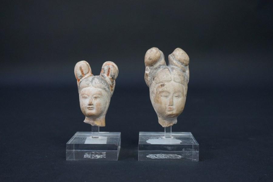 Deux petites têtes de dames de cour en terre cuite.