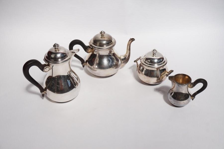 Service en métal argenté, anses en bois noirci, composé d'une théière, d'une cafetière, d'un pot-à-lait et d'un sucrier.