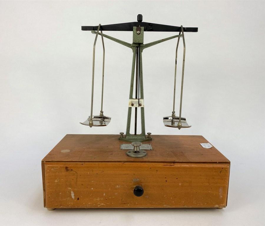Balance trébuchet de marque TESTUT type 335 (poids maximal 100 gr) avec ses poids. Bois et métal, taches d'usage. Années 1950. Environ 33 x 31 x 16 cm.