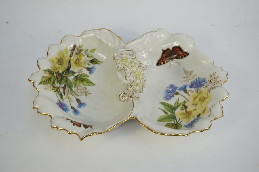 Coupelle en porcelaine à décor de fleurs et papillons. Signée CFH GDM Paris 1891 sous la base. 13 x 35 cm. Éclat en bordure.