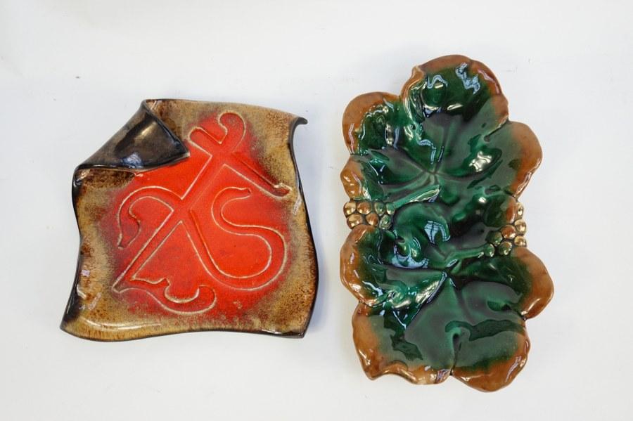 Dessous de plat dans le goût de VALLAURIS représentant une feuille repliée en céramique émaillée. Environ 26 x 27 cm. ON Y JOINT Un vide-poche à motif de feuilles et sarrements de vigne. 36 x 20 cm.