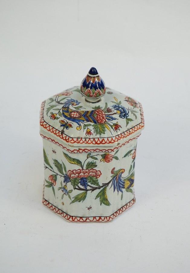 Pot couvert à panse facettée en faïence fine de Rouen à décor polychrome de cornes d'abondance fleuries. Égrenures et restaurations (prise recollée). H. : 18 cm.
