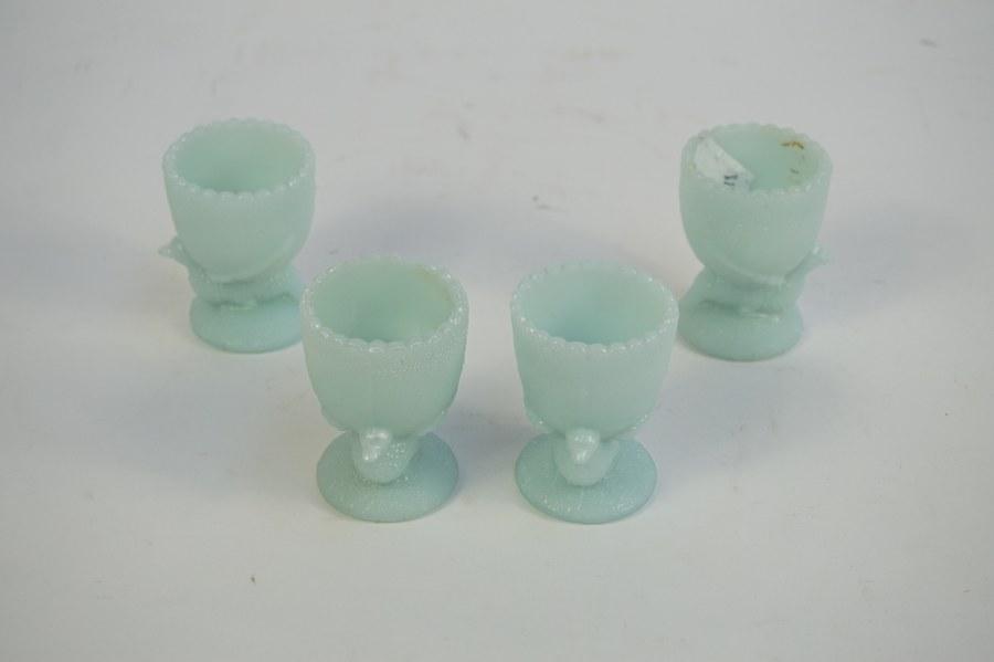 Quatre coquetiers en opaline bleutée moulée à décor de volatils.