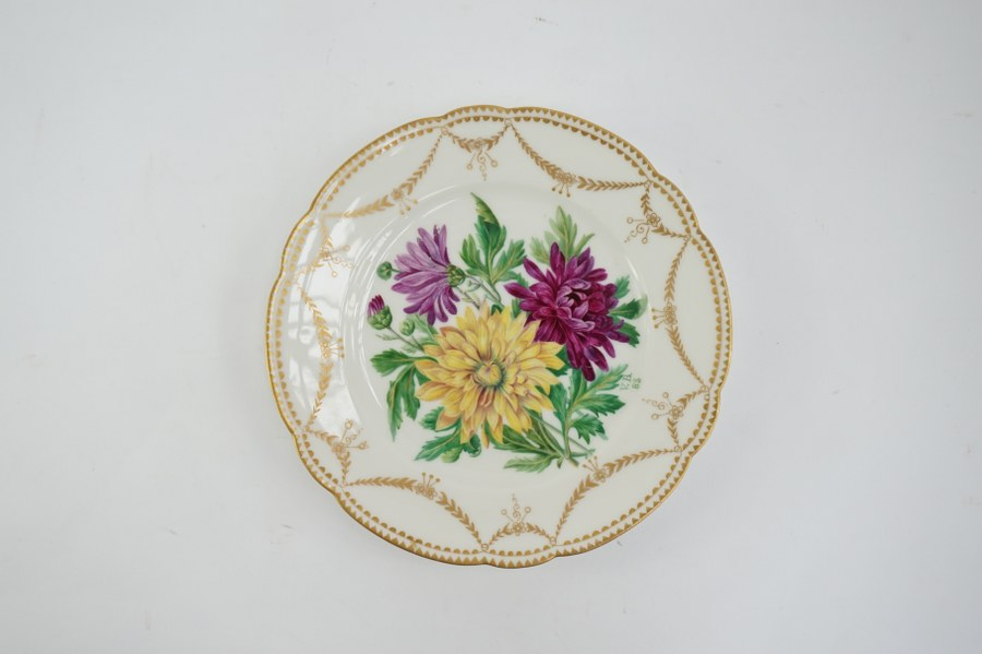Assiette en porcelaine à décor de chrysanthèmes peint à la main, signé V.B. daté 83. 21 cm de diamètre.