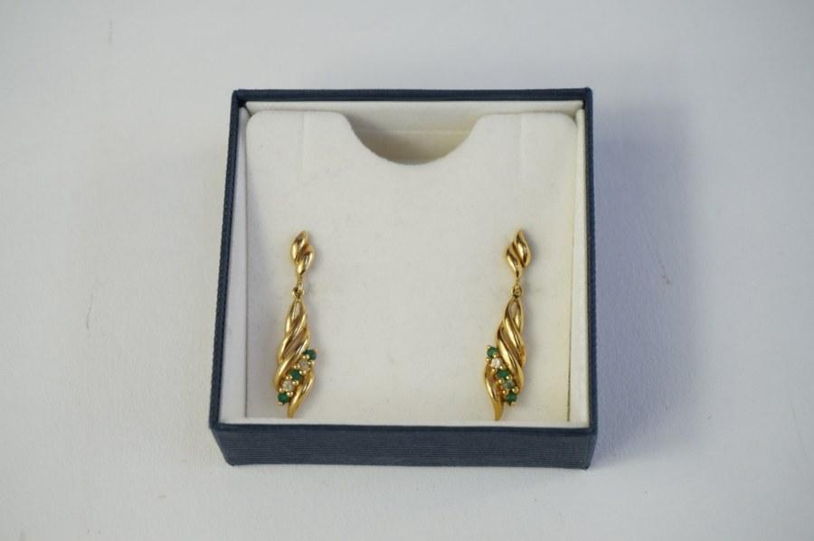 Paire de boucles d'oreilles en métal doré en forme de flamme serties de pierres vertes et blanches.