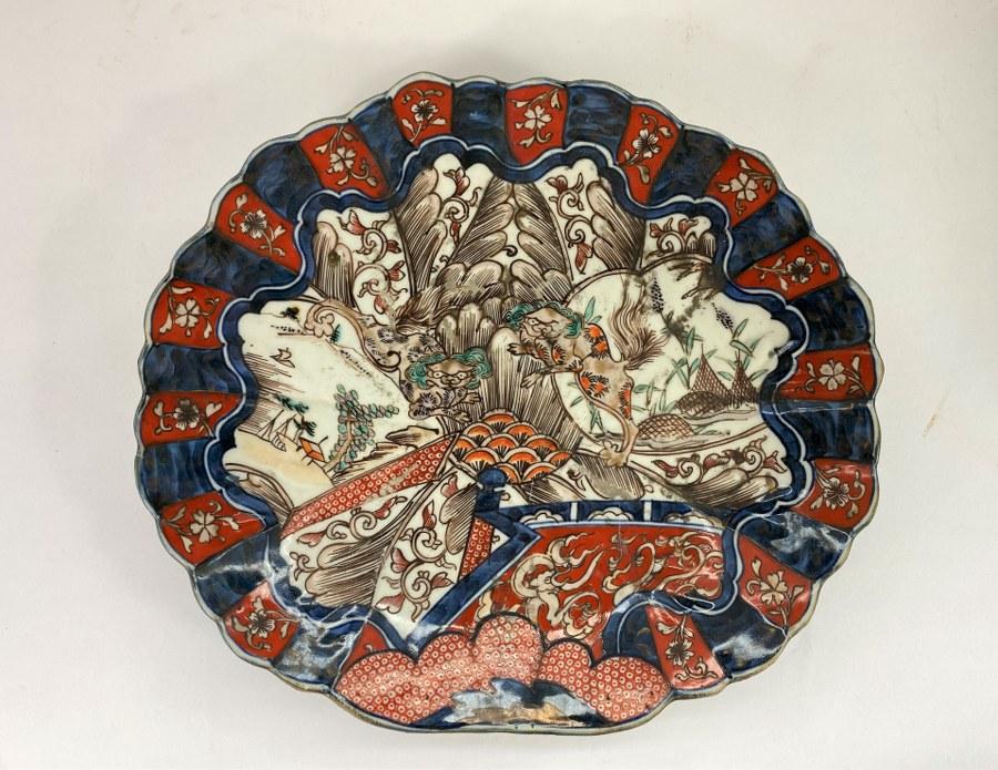 Plat en porcelaine Imari à décor de paysage asiatique. Usures.