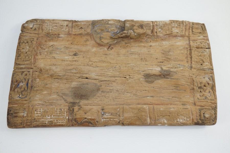 Plateau divinatoire Ifa YORUBA, ce premier figurant un visage se démarquant sur un liseré de motifs géométriques. Bois sculpté. XXe siècle. Nigéria. Accidents (état d'usage).