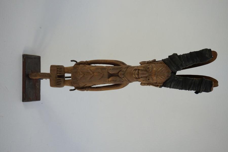 Lance-pierre figurant une femme vêtue d'une robe à décor de chevrons et au visage scarifié YOROUBA. Bois sculpté, cuir et caoutchouc. XXe siècle. Nigéria.
