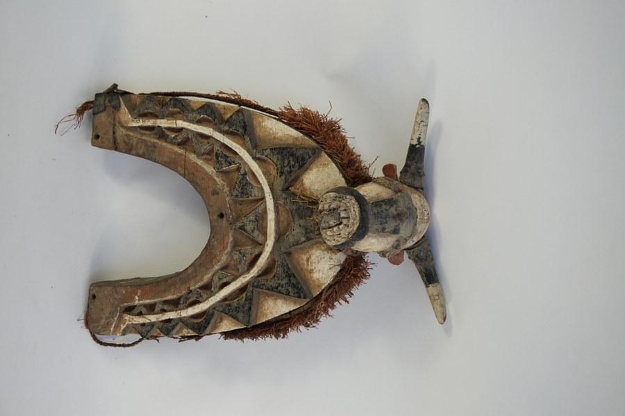 Maque de cou figurant un taureau avec un décor géométrique BIDJOGO. Bois sculpté peint de noir et de blanc, fibres végétales, verre. XXe siècle. Guinée-Bissau.