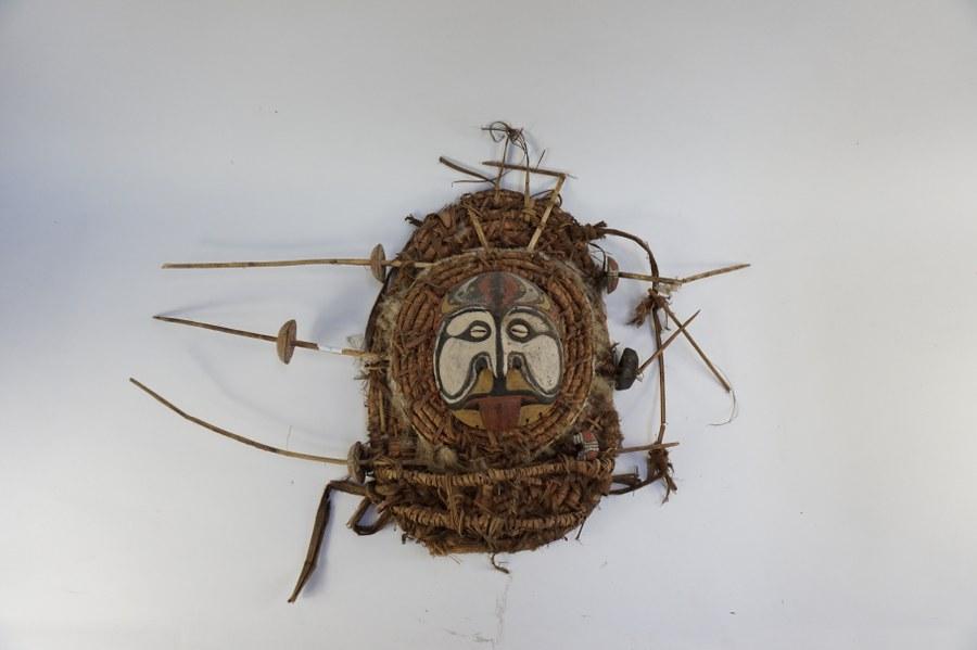 Masque de Papouasie-Nouvelle-Guinée figurant un visage à la langue tirée (culture du fleuve Sepik). Bois sculpté polychrome jaune, blanc, noir et rouge, yeux en cauries, fibres végétales. XXe siècle. Accidents.