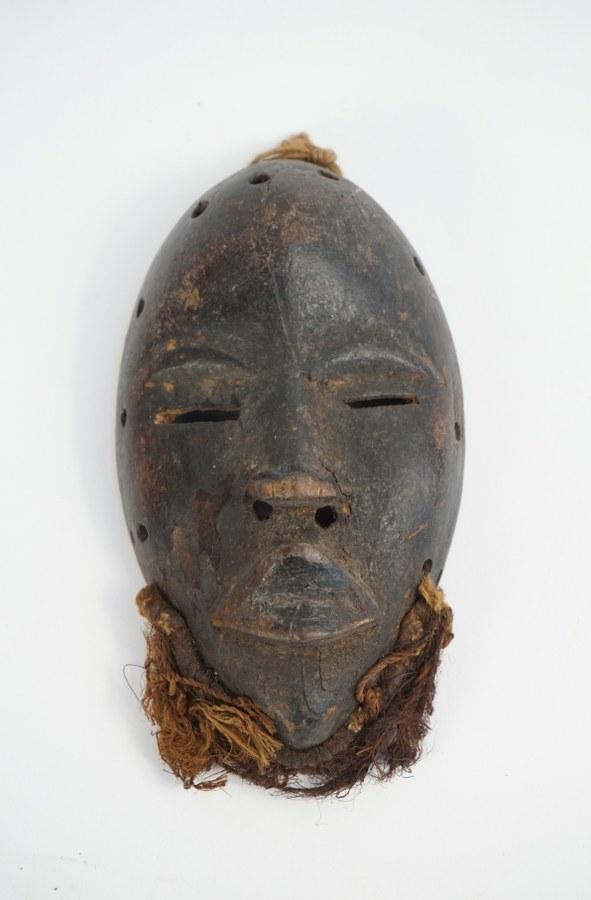 Petit masque DAN figurant un visage. Bois sculpté patiné, fibres végétales. XXe siècle. Côte d'Ivoire.