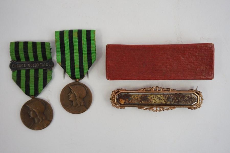 Épingle à cravate en métal doré, dans sa boîte. ON Y JOINT Deux médailles.