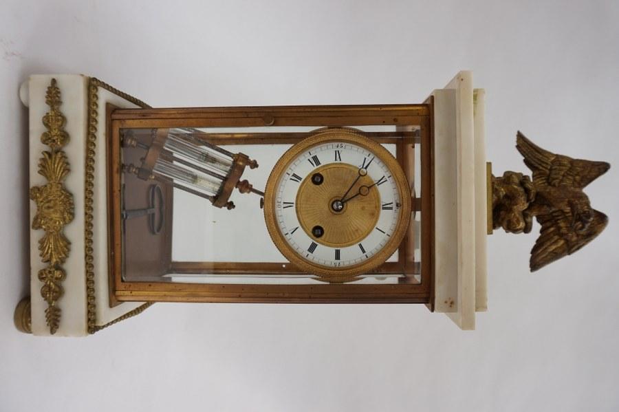 Pendule cage en verre, bronze doré et marbre blanc. Décorée d'un aigle, balancier au mercure. XIXe siècle. H : 43 cm.