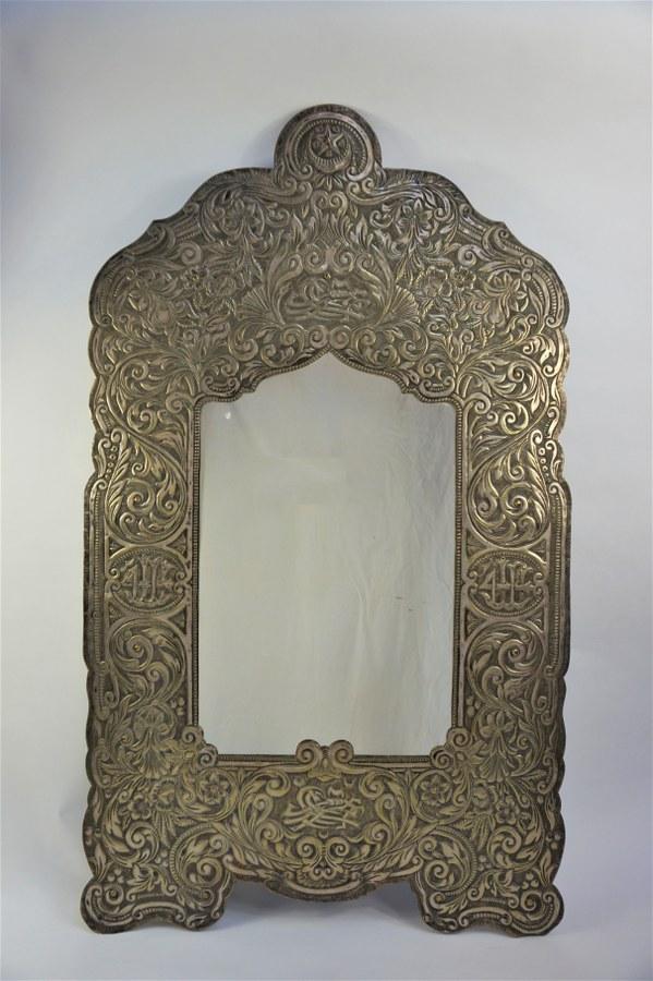 Miroir en laiton repoussé à décor de fleurs. H : 105 cm.