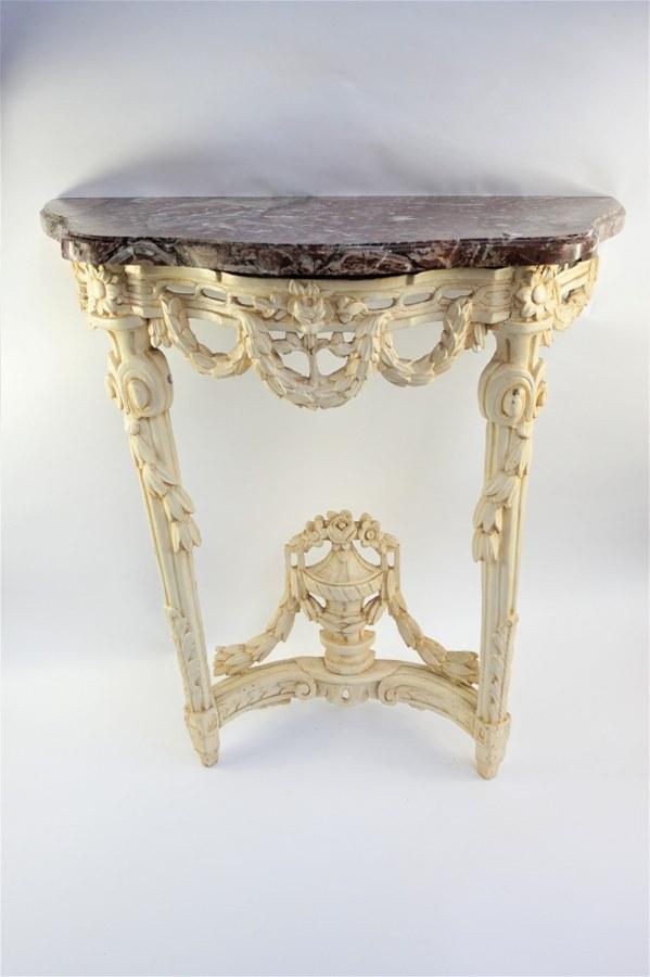 Console en bois laqué blanc à décor de guirlandes fleuries. Bois peint beige et marbre. XVIIIe siècle. 83 x 76 x 36 cm. Accidents et restaurations.