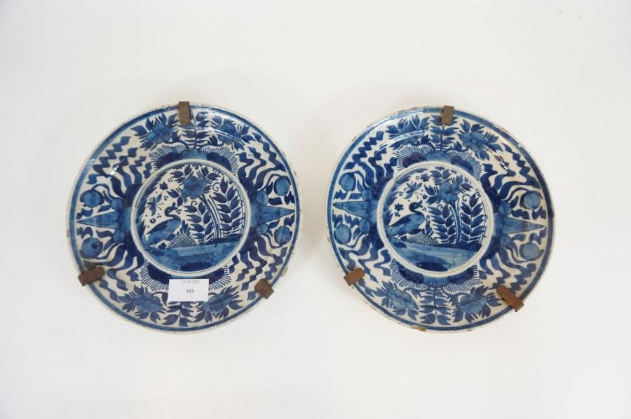 Paire d'assiettes décoratives à motif de canard et verdures en faïence fine dans le goût de Delft. Fin du XVIIIe - Début du XIXe siècle. Egrenures.