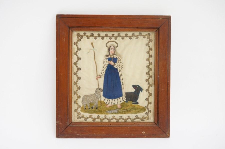 Ex-voto avec une sainte bergère accompagnée d'un chien noir et d'un mouton. Broderie sur soie aux fils textiles et métalliques, carnations peintes. Cadre : 37,5 x 35 cm.