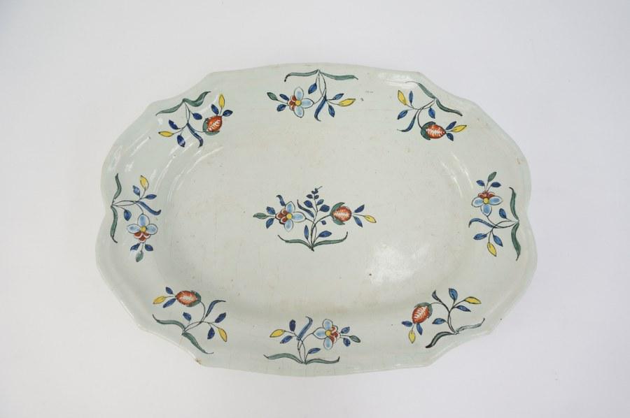 Plat ovale à bordure chantournée en faïence de SINCENY à décor de semi de fleurs. XVIIIe siècle. Rayures d'usage.
