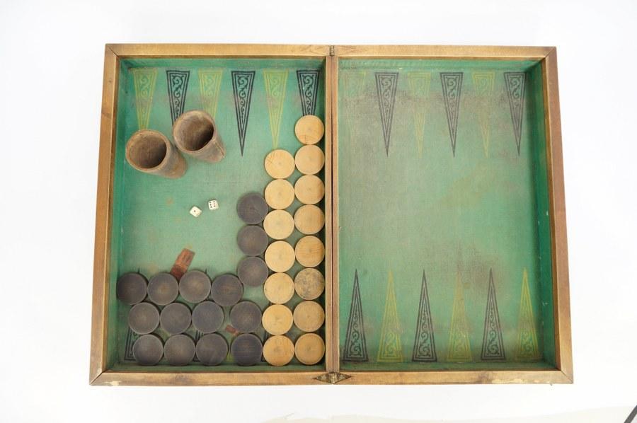 Coffret à jeu de tric-trac refermable en bois de placage sur bâti de sapin, pièces en buis et sapin teinté, deux gobelets de cuir et dés en ivoire. Fin du XIXe - Début du XXe siècle. Accidents et sauts de placage.