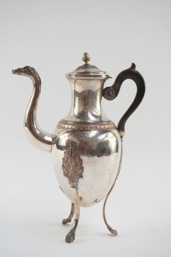 Cafetière tripode en métal argenté à décor de style Néoclassique Empire. Accident au couvercle.