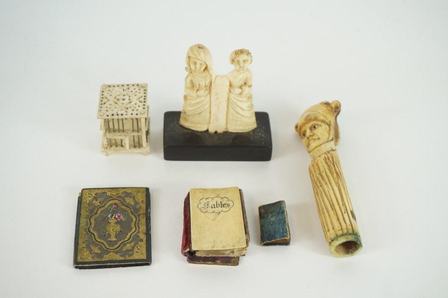 Lot de livres miniatures dont un avec une couverture en os, cage miniature en os, manche en forme de personnage en bois de cerf, relief de style XIIIe siècle en os. XIXe - XXe siècle.