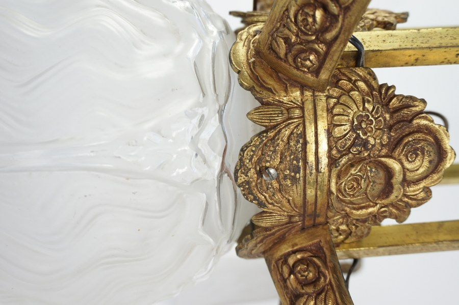 Plafonnier Art déco à décor de fleurs et guirlandes à quatre abat-jours de verre biseauté, globe central en verre moulé pressé. Accidents, égrenures. 75 x 40 x 40 cm.