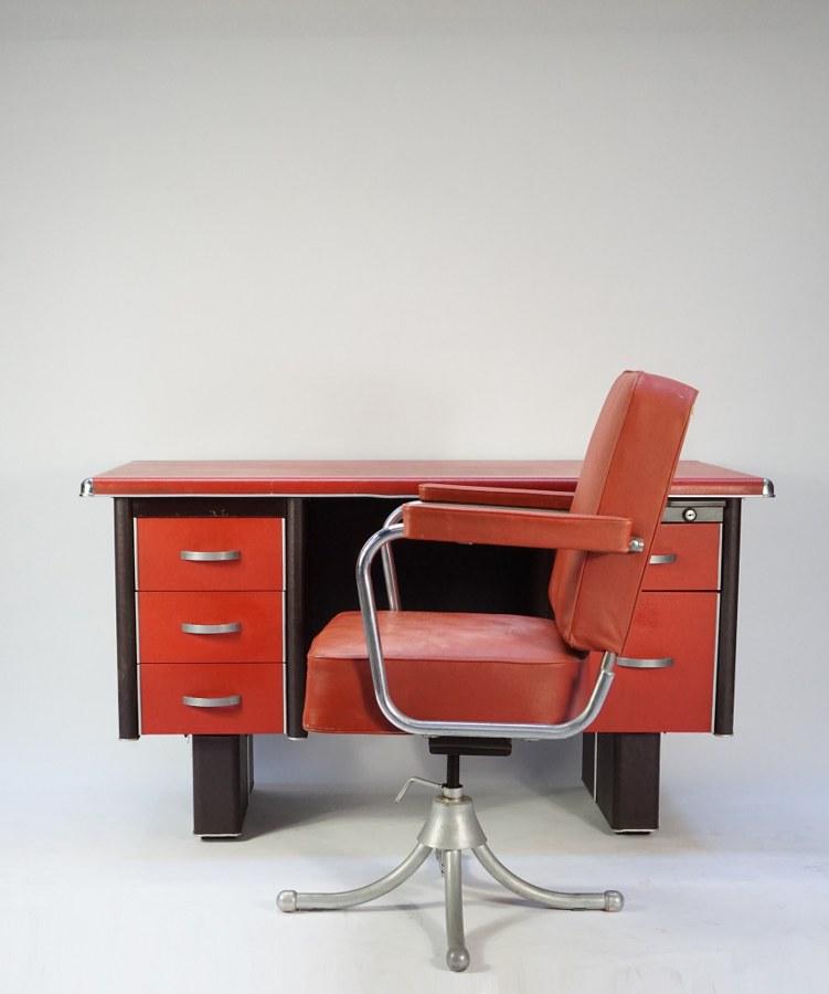 Dans le goût de Willem Hendrik GISPEN (1890-1981). Bureau plat à double caissons et fauteuil à assise pivotante. Structure en métal gainée de cuir rouge et noir et métal chromé. Années 1950-1960. Usures du cuir sur le fauteuil.