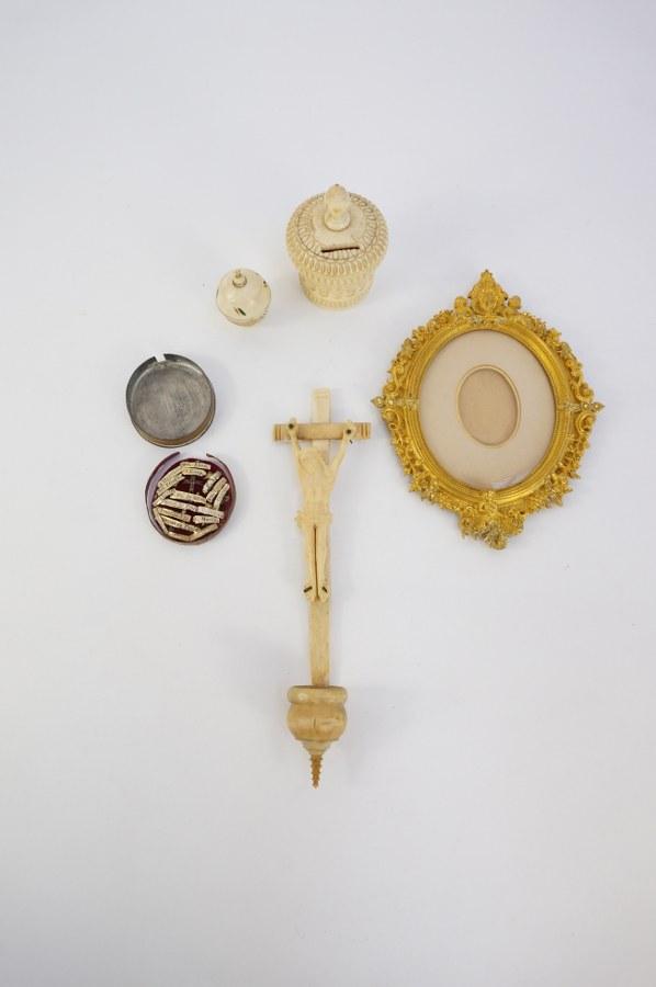 Lot comprenant une boîte à chapelet, une boîte à aumônes, un crucifix en os et un petit reliquaire. ON Y JOINT Un cadre ovale en métal doré à riche décor éclectique. XVIIIe - XIXe siècle.