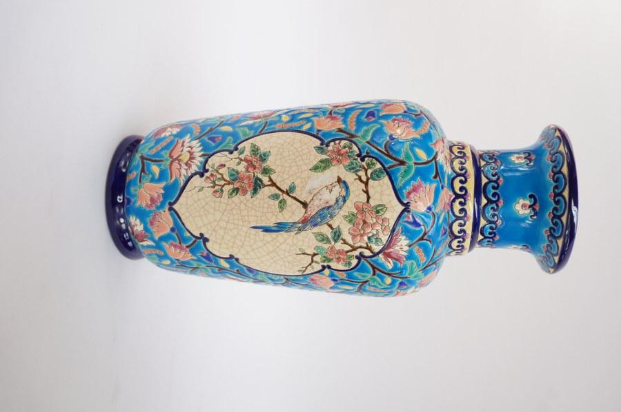 Grand vase en faïence glaçurée polychrome dite émaux de LONGWY à décor de rinceaux sur fond bleu entourant des médaillons avec un oiseau sur une branche fleurie. Marqué LONGWY sous la base. Années 1970 - 1980. H. 42 cm.