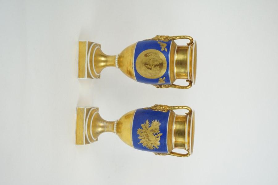Paire de vases en porcelaine de Paris à décor de médaillons et trophées sur fond bleu. Première moitié du XIXe siècle. H. : 26,5 cm. Petits accidents.