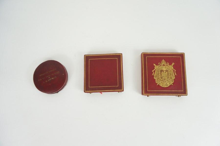Lot de trois médailles en bronze dans leurs écrins aux effigies de Louis XVIII et Napoléon III. L'une décernée à un instituteur avec pour légende ''Dans le pays du Suffrage Universel, tout citoyen doit savoir lire ou écrire''. XIXe.
