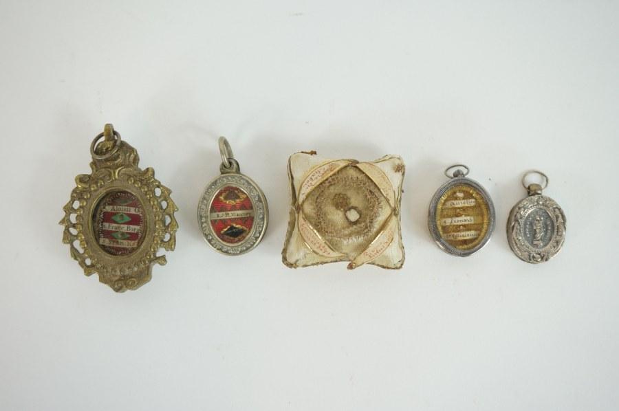 Ensemble de reliquaires. Comprenant quatre pendentifs et un coussin.