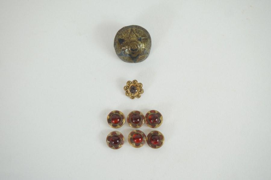 Suite de six boutons sertis de cabochons rouges. On y joint deux boutons.