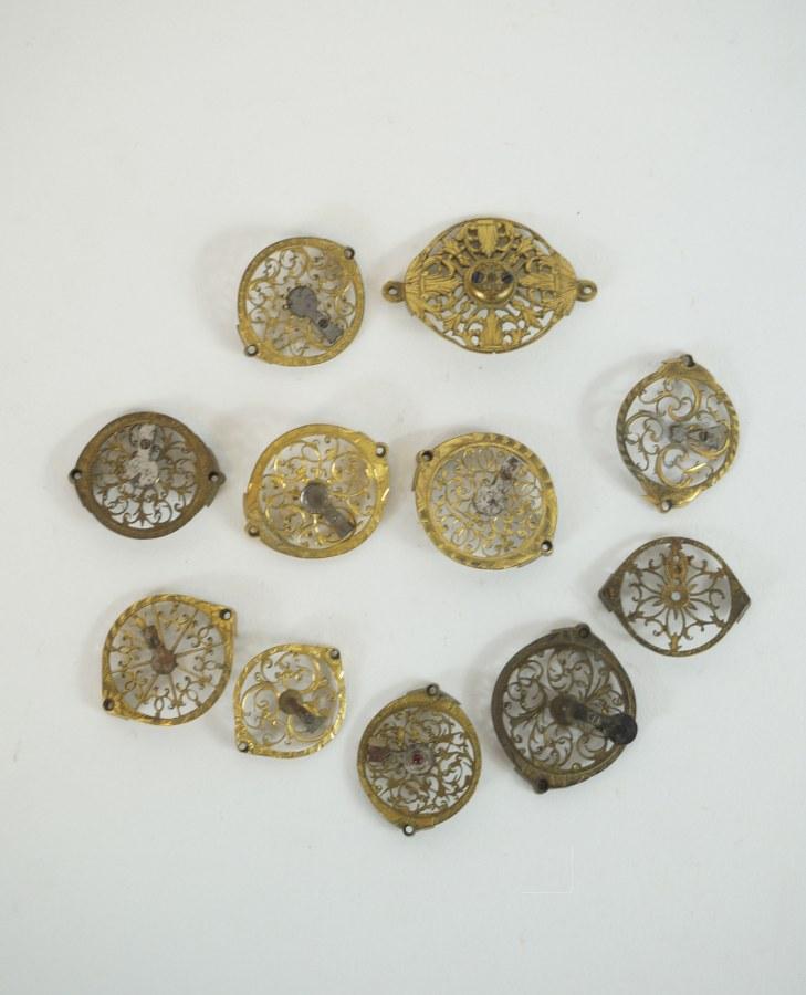Onze platines de montres ajourées en métal doré à décor de rinceaux. XVIIIe-XIXe siècle.