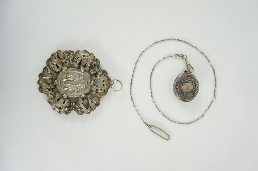 Pilulier en argent relié à une chaîne en métal, à décor de guirlande de laurier et relief votif en décor d'entrelacs ajourés. Travail du XIXe siècle.