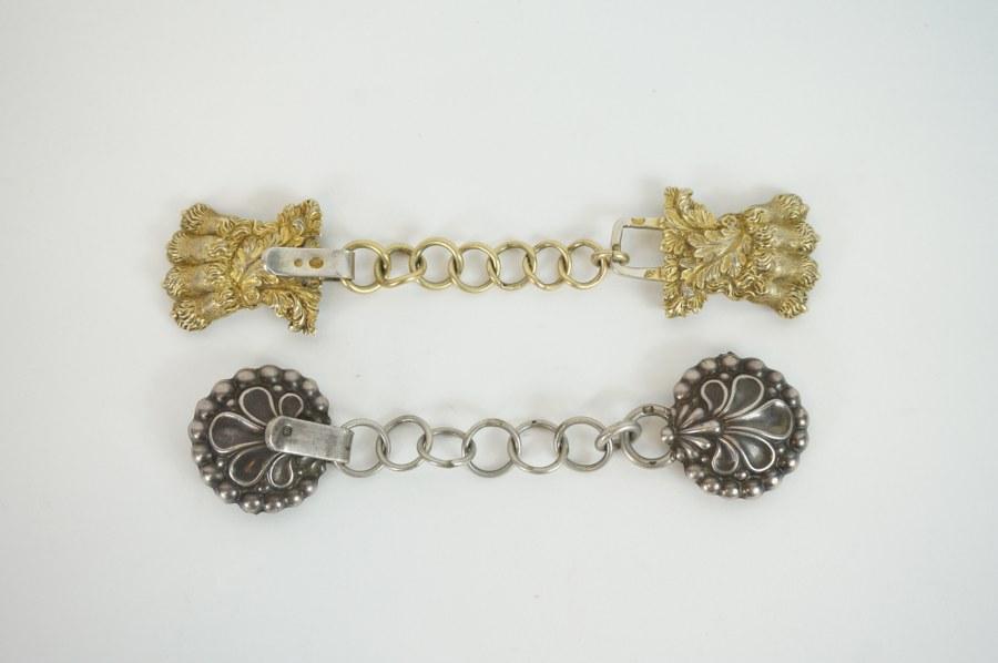 Deux attaches de cape. Une en vermeil à décor de pattes de lion et la seconde en argent à décor de palmettes. XIXème siècle.