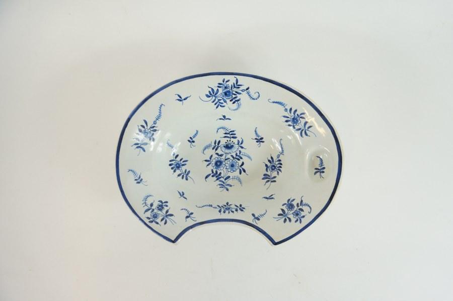 Plat à barbe en faïence dans le goût de Nervers à décor bleu de bouquets de fleurs. Fin du XIXe - Début du XXe siècle. 7 x 20 x 27 cm.