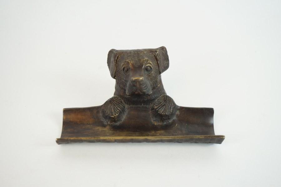 Porte-plume porte-crayon à motif de protome de chien en bronze patiné. 8 x 16 cm.