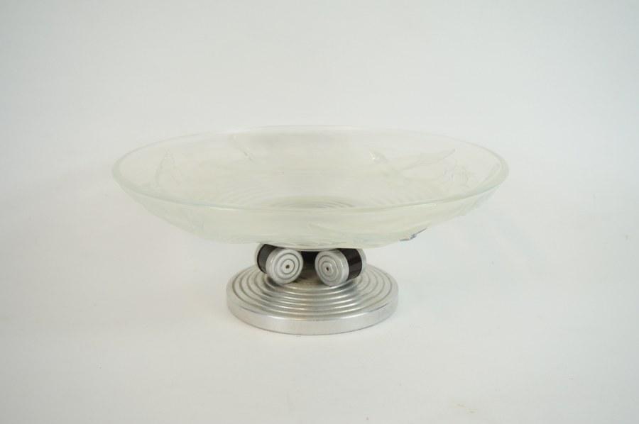 A. MIGUEL (XXe). Dans le goût de ETLING. Coupe sur pied en verre moulé à motif tournoyant d'oiseaux, piétement de bois et métal en à trois cylindres soutenus par une base circulaire moulurée Art Déco. Verre marqué AM Années 1930. H. : 12,5 cm. Diam. : 32 cm.