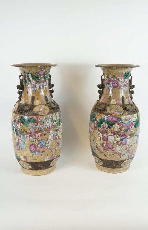 Paire de vases en porcelaine de Nankin à décor de scènes de batailles et motifs de dragons en reliefs. XIXe siècle. H. : 44,5 cm. Lèvres accidentées, petits éclats sur les panses.