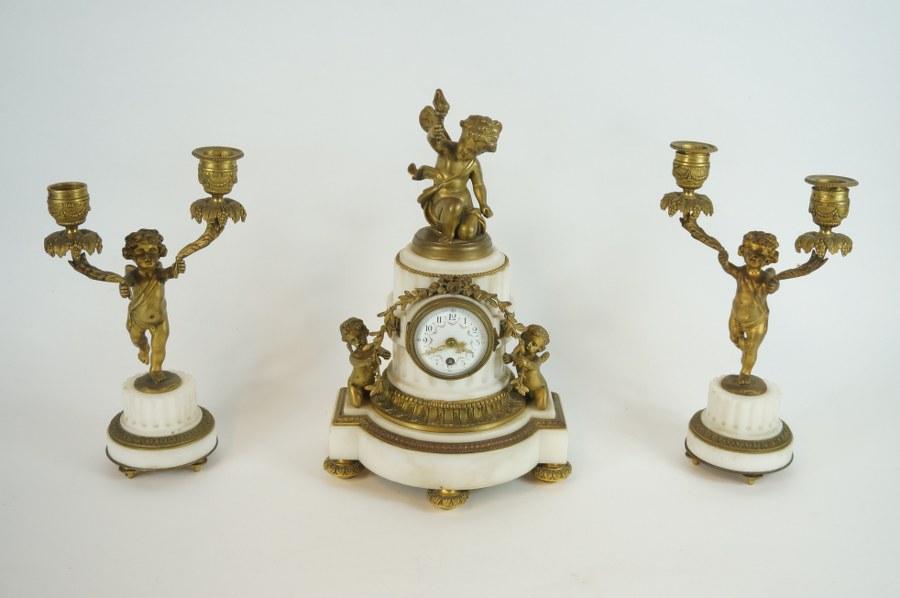 Garniture comprenant une pendule en marbre blanc et décor de putti et guirlandes en bronze ciselé doré et une paire de bougeoirs à deux bras de lumières. Travail du XIXe. H. : 31 cm (pendule) Petit accident au cadran, mécanisme manquant.