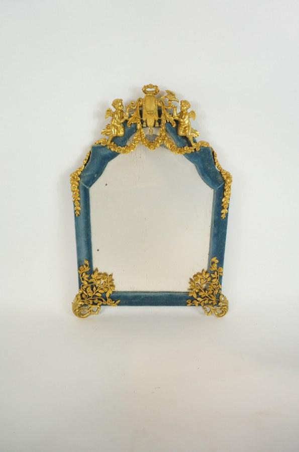 Glace à poser garnie de velours bleu à décors de rinceaux de roses et putti en bronze doré. Seconde moitié du XIXe siècle. H. : 37 cm. Support arrière manquant.